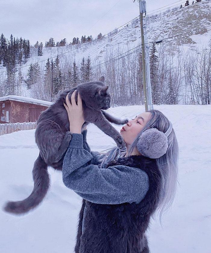 девушка в наушниках держит серого кота на руках
