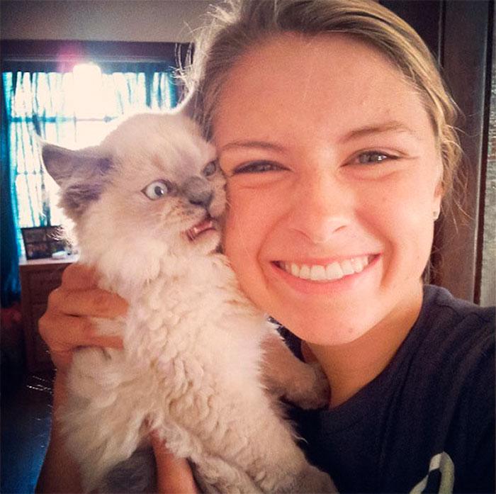 недовольный кот на руках у девушки