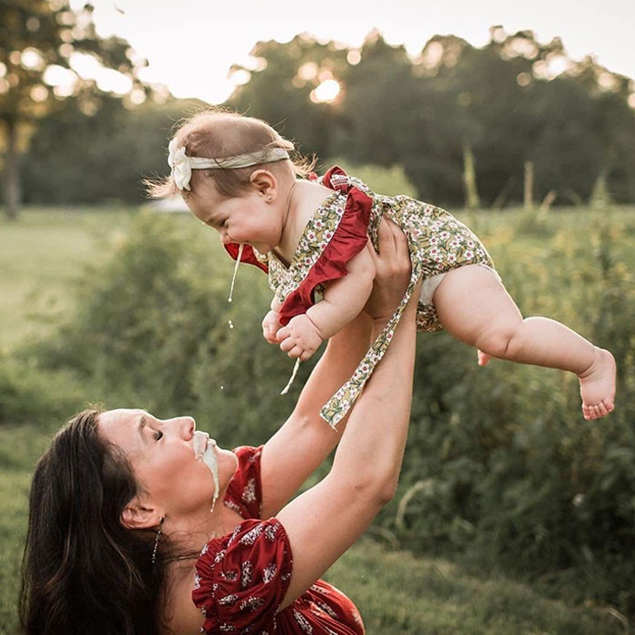 мама держит дочь над головой