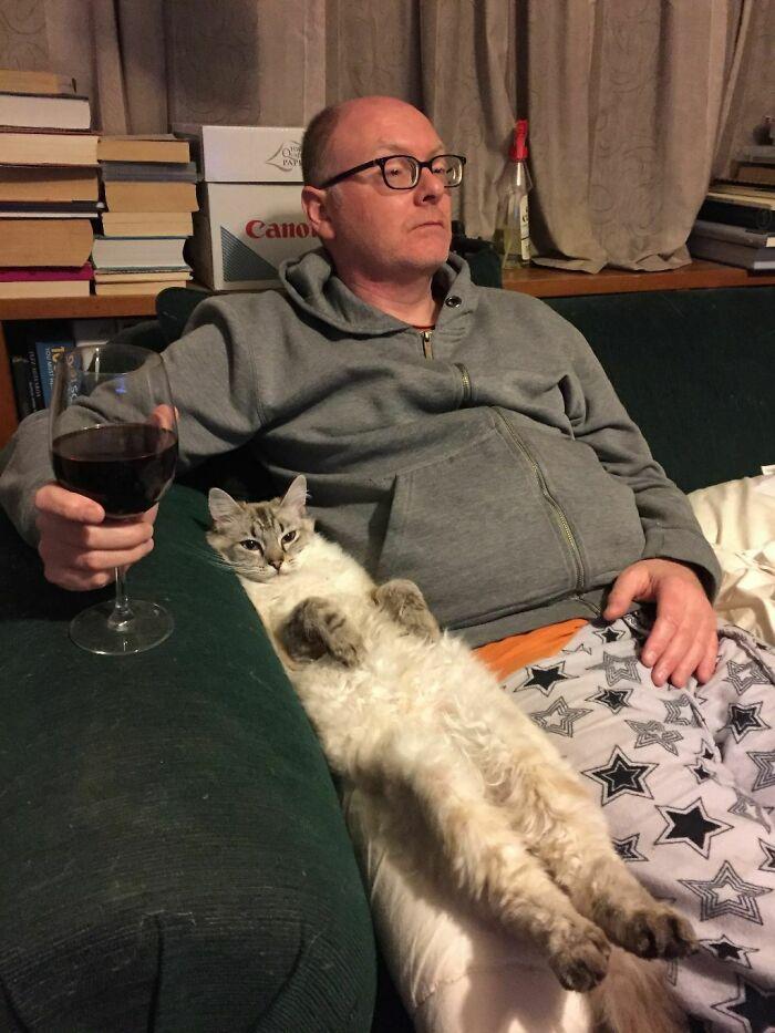 мужчина в очках с бокалом вина и кот