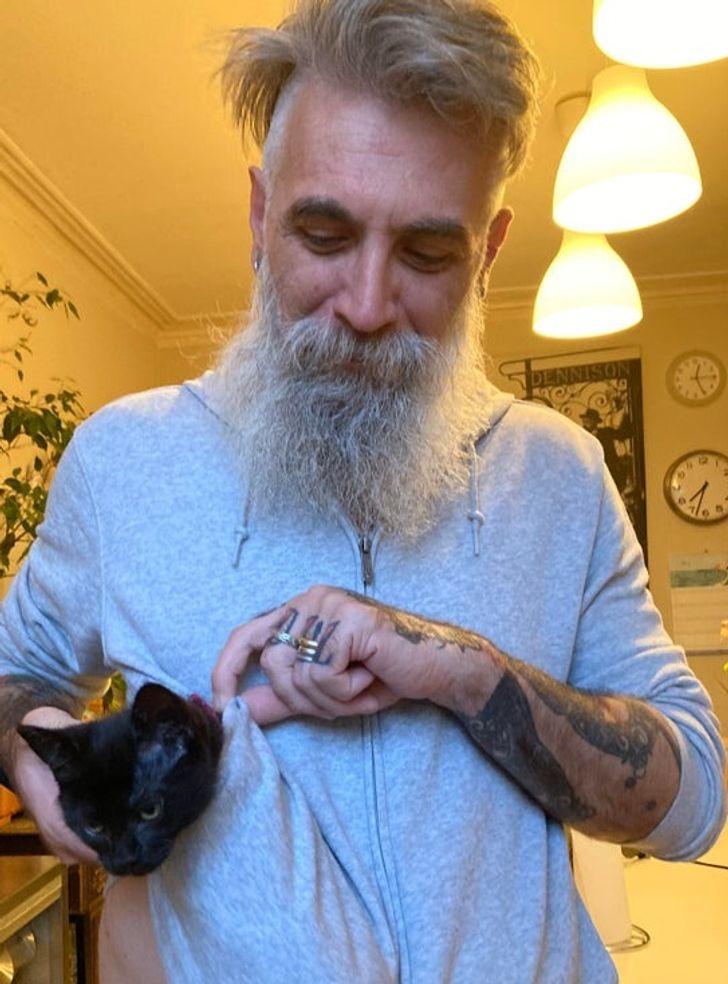 бородатый мужчина с черным котенком в кармане