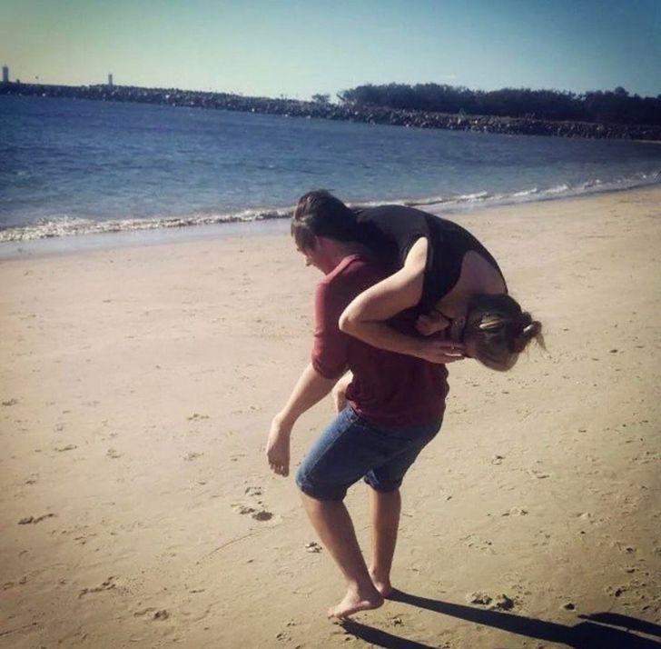 парень несет девушку на плече к морю