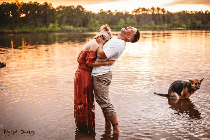 пара смеется, стоя в воде, с собакой на заднем плане