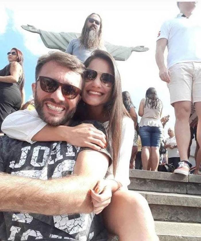 пара делает селфи на фоне статуи христа